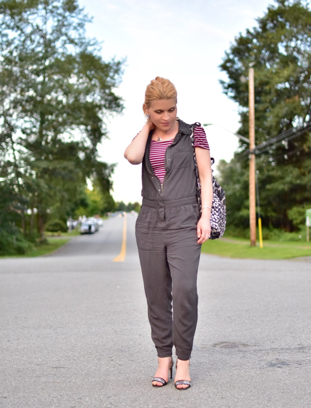 styling a sleeveless jumpsuit with a striped t-shirt, ankle-strap heels, and a leopard-print backpack