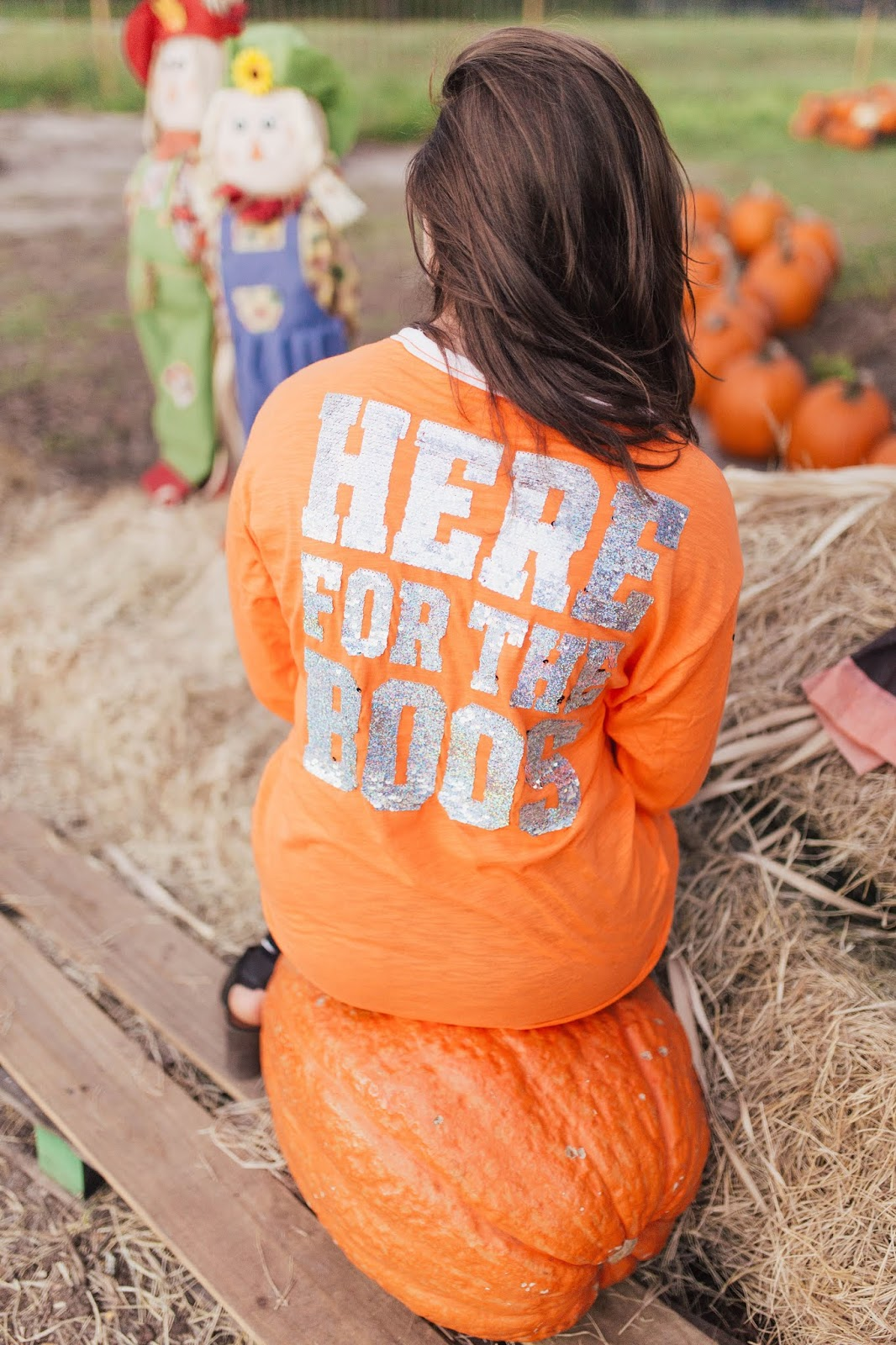 Brunette girl wearing Victoria's Secret Pink Here For The Boos studded bling campus long sleeve lace up tee at pumpkin patch in jacksonville florida