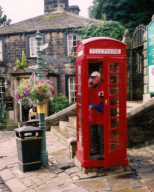 man in a red phone box, in Haworth, Yorkshire