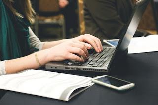 A woman writes on a laptop upon a black desk