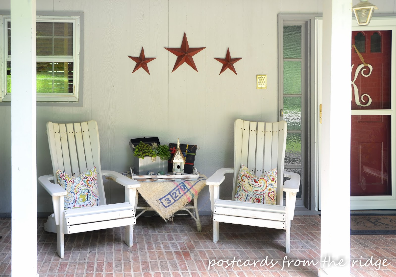white Adirondack chairs with outdoor pillows and summer decor