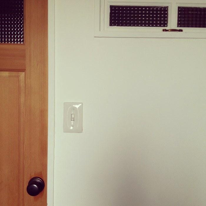 リノベーションマンションの陶器製スイッチとドアとチェックガラスの小窓