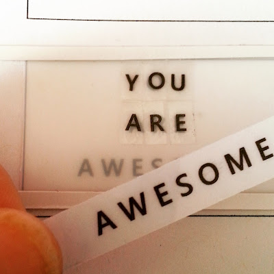 Words 'You are awesome' printed out and being attached to a miniature light box front.