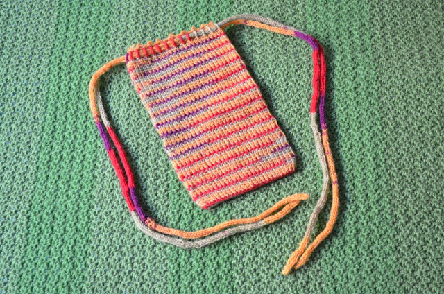 Rectangular crocheted bag with drawstring across the top.