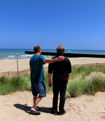 two men standing on a beach