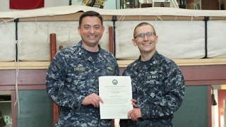 LCDR Peter Hoegel congratulates Petty Officer Mong
