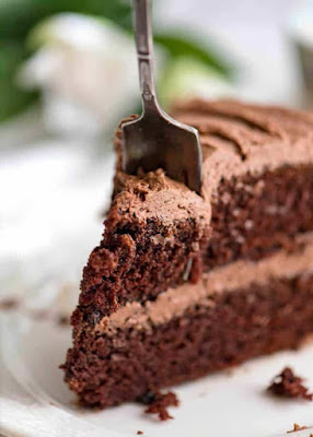 Close up photo of a slice of Chocolate Cake with Buttercream Chocolate Frosting on a white dessert plate with a fork partially cutting into it.