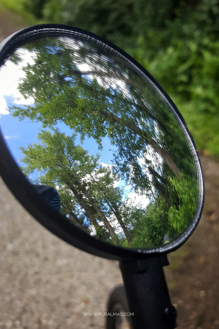 green trees reflected in a bike mirror www.ruralmag.com