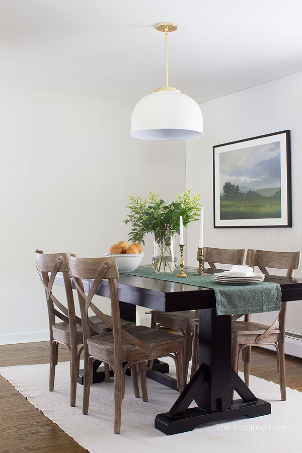 Farmhouse dining room with white vertical tongue and groove, black table, whitewashed wood chairs, large landscape art, and green table runner. Modern traditional style decor.
