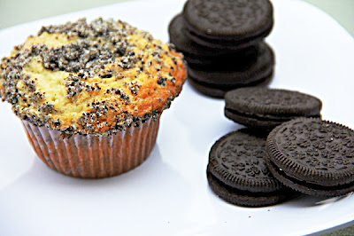 muffins with an oreo streusel on top and stacks of oreos next to it