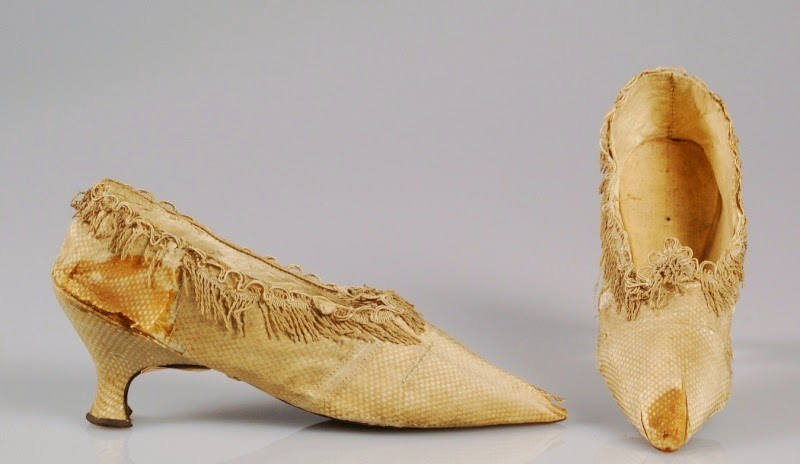 side view of Marie Antoinette shoes, fringe along the top and a water stain on one shoe