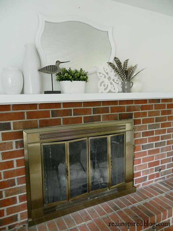 A fresh spring mantel decorated using plants and feathers and set against alabaster white walls.