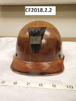 Safety helmet with brown textured coating, short brim, and bracket on front for a lamp - catalog number CF2018.2.2 is at top of photo
