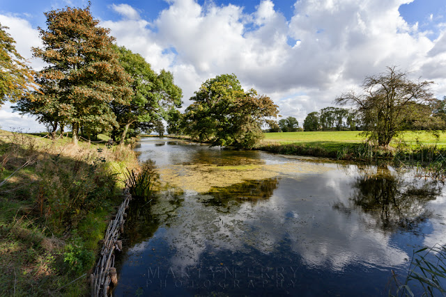 Trees and clouds reflected in the 400 year old moat at Lyveden New Bield