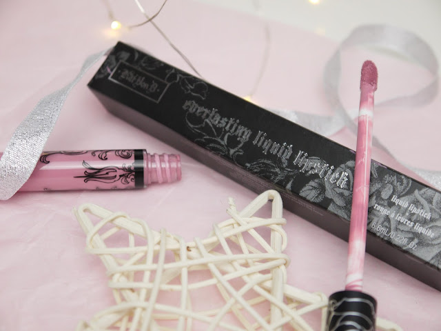 a tube filled with lilac lipstick and patterned with black and silver designs