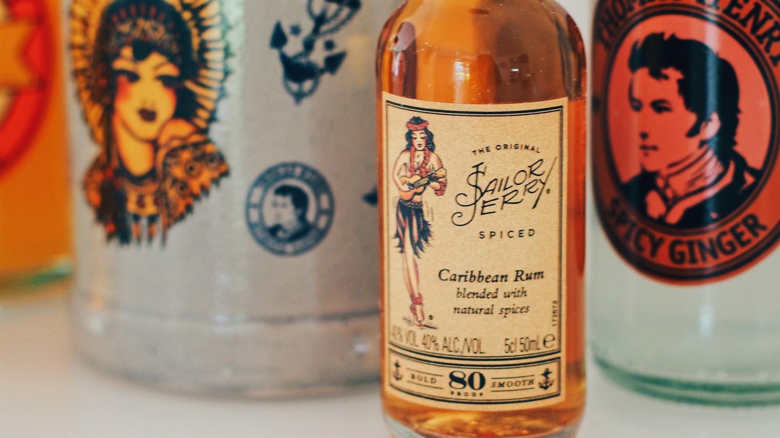 Sailor Jerry Rumflasche 4cl vor dem Sailor Jerry Krug umrandet von Thomas Henry Fillern