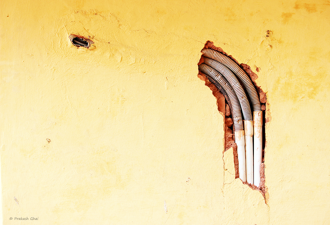 A Minimalist Photo of Electrical pipes coming out of a cement wall at Jantar Mantar Jaipur, during repair work.