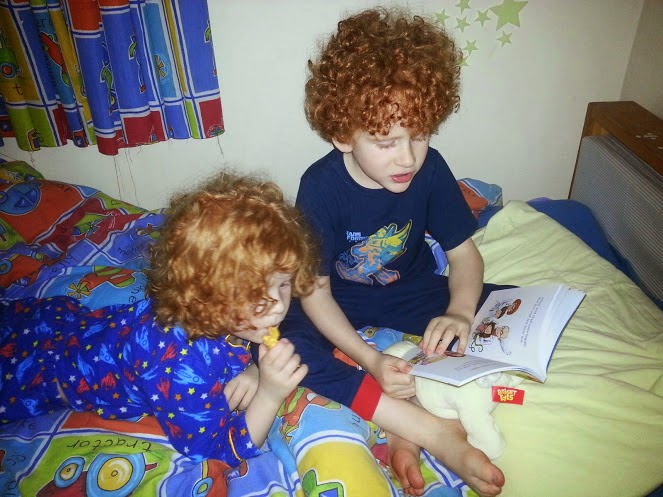 6 year old reading to his little brother in bed