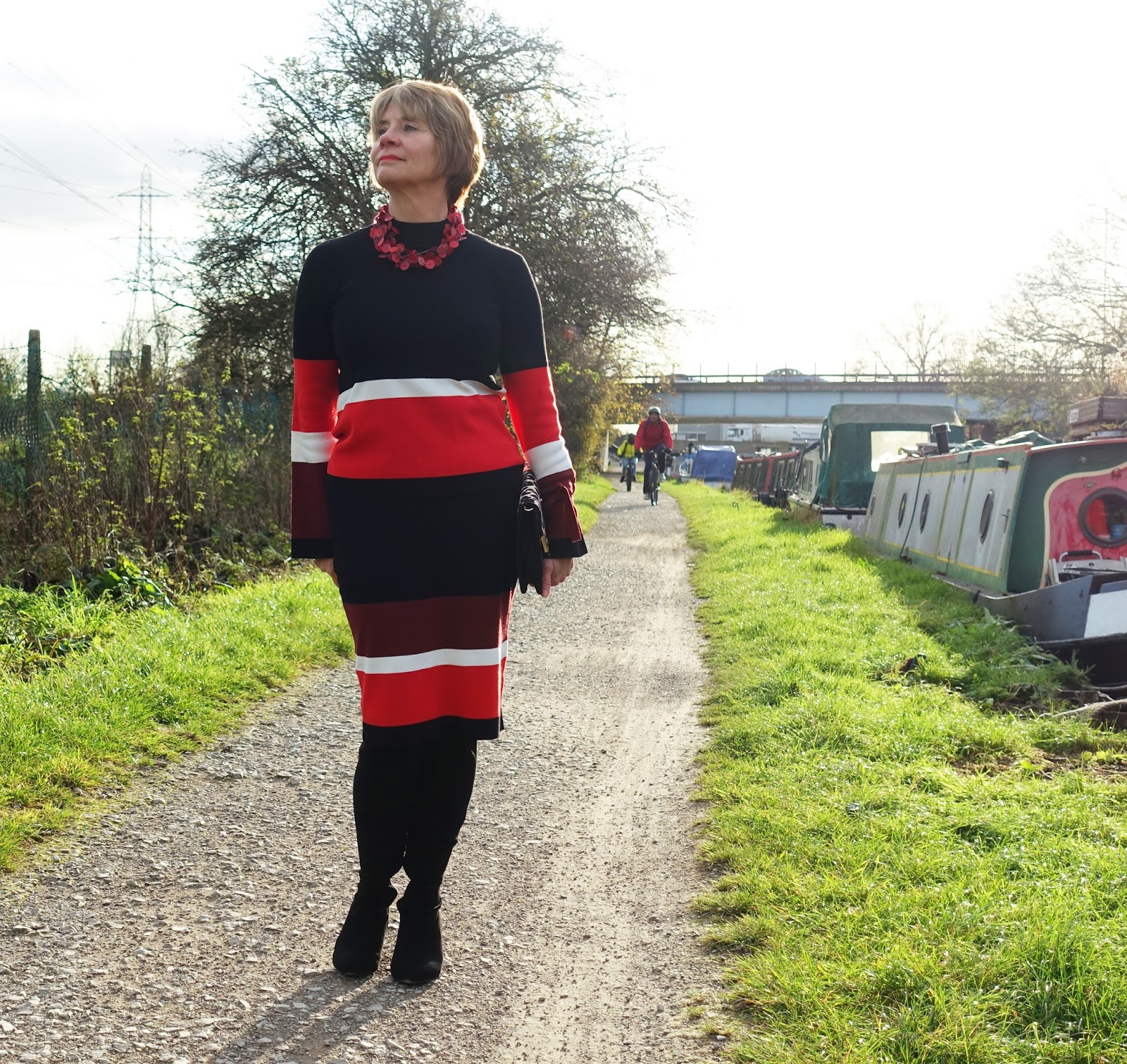 Image showing a woman in her 50s by a canal wearing black over the knee boots and a black maroon and paprika red jumper and knee length skirt