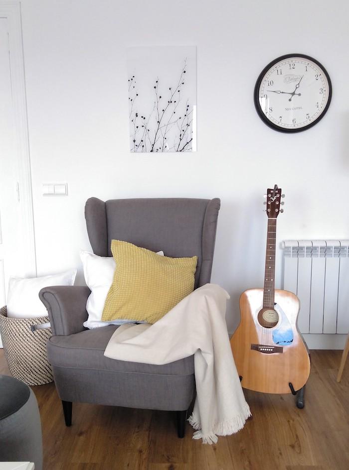 sillón orejero y lámina escandinava en la pared