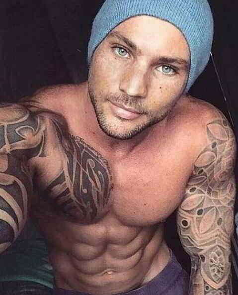 Imagen de un hombre con tatuajes de mandalas