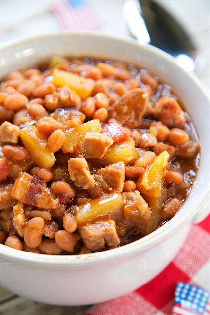 Slow Cooker Baked Beans - absolutely THE BEST baked beans! Bacon, baked beans, onion, mustard, bbq sauce, smoked pork and the secret ingredient - pineapple! SO good! I could make a meal out of these delicious beans! They slow cook all day in the slow cooker. Great for a potluck crowd. Took these to a cookout and everyone asked for the recipe!