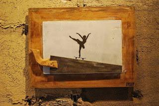 A fotografia mostra um quadro retangular em uma parede com reboco inacabado pintado em tom mostarda. A moldura é em madeira clara e manchada, a tela em fundo branco, ao centro, em preto, a silhueta de uma bailarina com pé esquerdo na ponta, sobre um skate que desliza sobre a parte dentada de um serrote sobreposto à base da tela com o cabo à esquerda e voltado para cima, cobrindo parte da moldura. A bailarina usa um tutu, está com a cabeça direcionada para cima, braços abertos ao alto, tronco inclinado à frente, perna direita para trás e ao alto. No canto inferior direito da moldura, a assinatura do artista: Tyler.