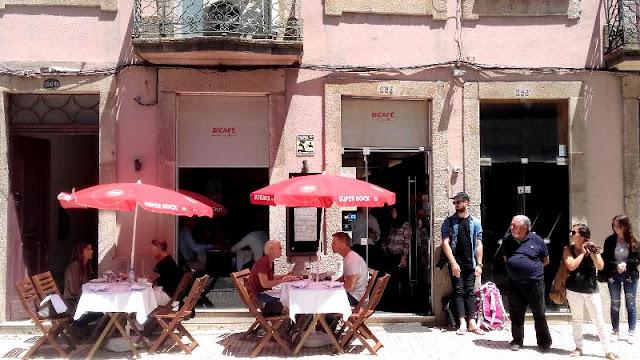 esplanada de restaurante com muitas pessoas sentadas e a espera