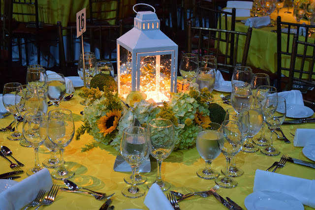 summer flowers, sunflowers, moss, lantern centerpiece, hydrangea, yellow and green centerpiece