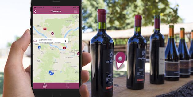 Mano sostiene celular con aplicación abierta y botellas de vino de fondo