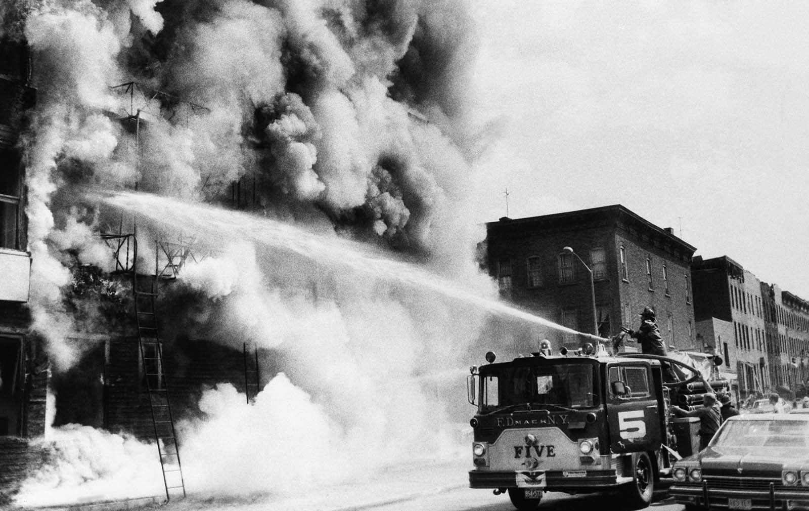 Firemen fight a blaze above a row of looted stores in New York's Brooklyn borough, July 14, 1977, the day after the power failure. The stores were looted during blackout.