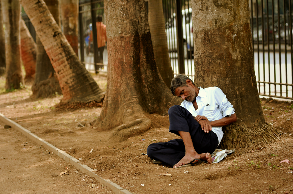 Man in Mumbai, India is sleeping in the Oval Maidan, which is a large recreational park in Mumbai, India.