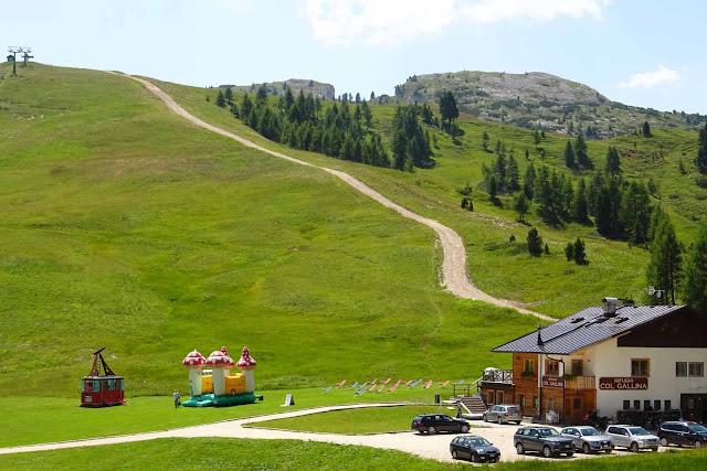 Rifugio Col Gallina am Falzaregopass mit Sonnenliegen, Kinderhüpfburg, Parkplatz, Grünen Wiesen und Bergketten