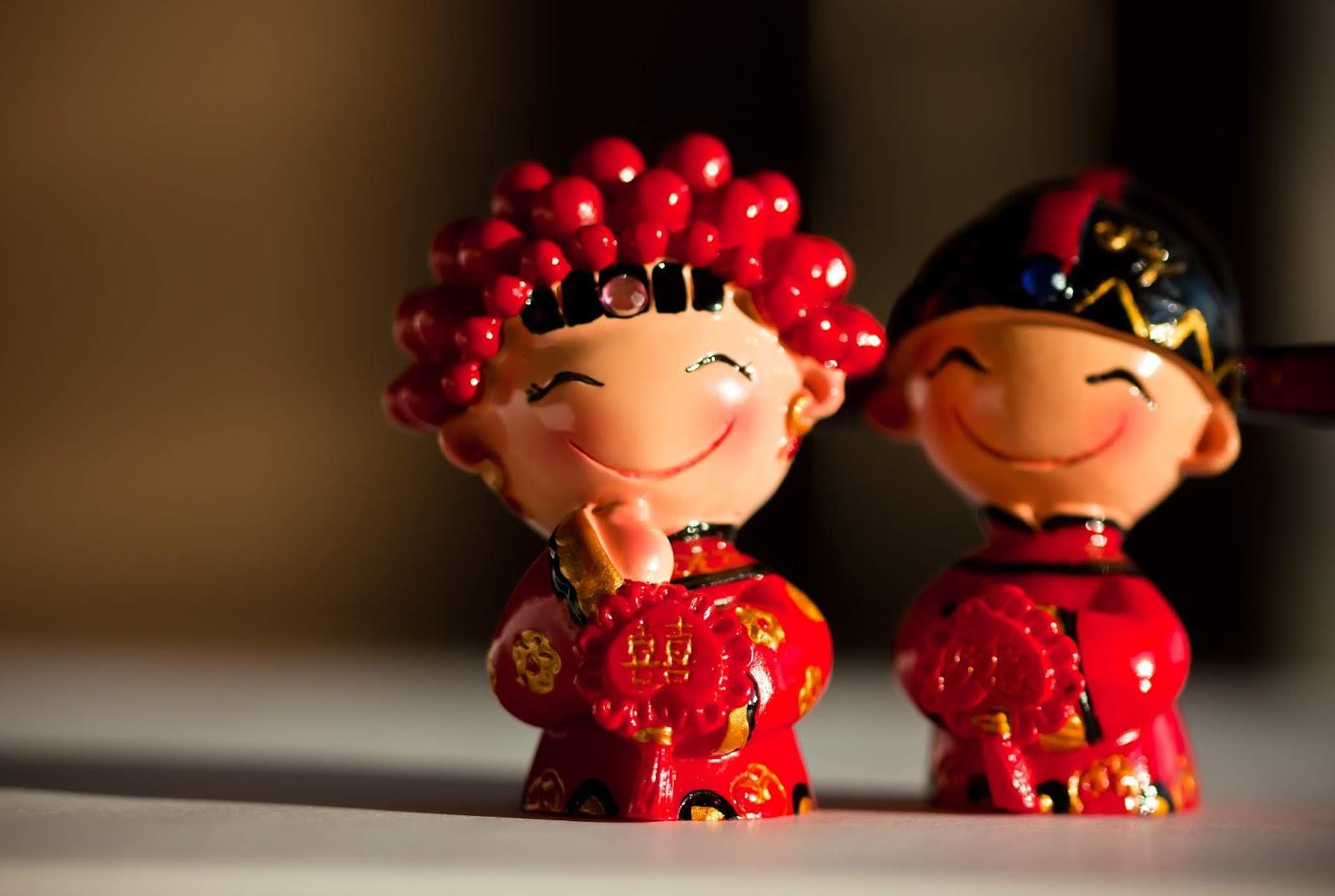 Superstições chinesas - bonecos feminino e masculino representando um casamento chinês com roupas tradicionais vermelhas