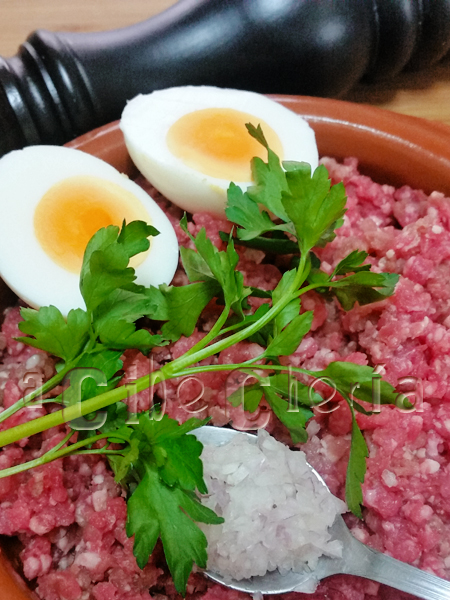 Huevos rellenos con carne, rebozados y fritos, acompañados con salsa verde de perejil