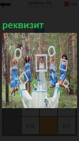 На поляне девушки с реквизитом подпрыгивают в верх, стоит стол и стул