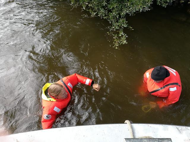Kaksi henkilöä pelastautumispuvuissaan vedessä.