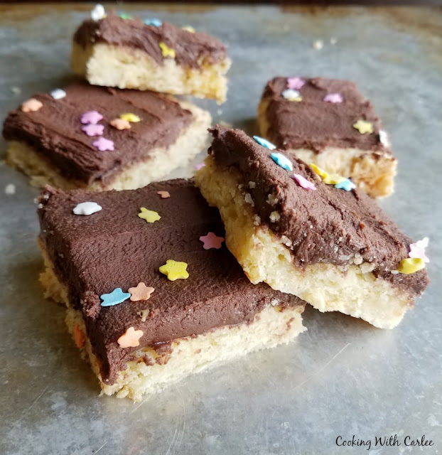 square pieces of sugar cookie bars with chocolate frosting and star sprinkles on top piled on baking sheet