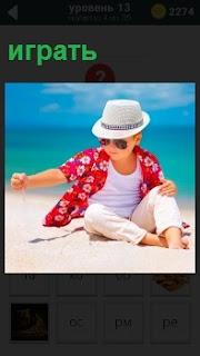 Мальчик в шляпе играет на берегу в песок в солнечный день, одев очки и красную рубашку с белыми штанами