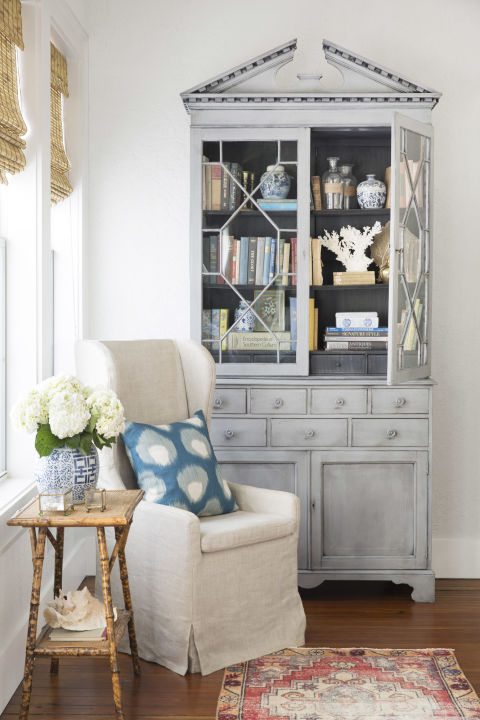 A tranquil living room with farmhouse style in a charming Texas cottage by Holly Mathis. Blue grey painted tall Secretary cabinet and a natural linen slipcovered wing chair create a cozy reading corner. #decorating #farmhouse #cottagestyle #paintedfurniture #livingroom #wingchair