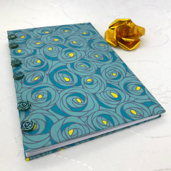 hand bound hardcover book with blue and yellow rose patterned cover and blue glass rose buttons