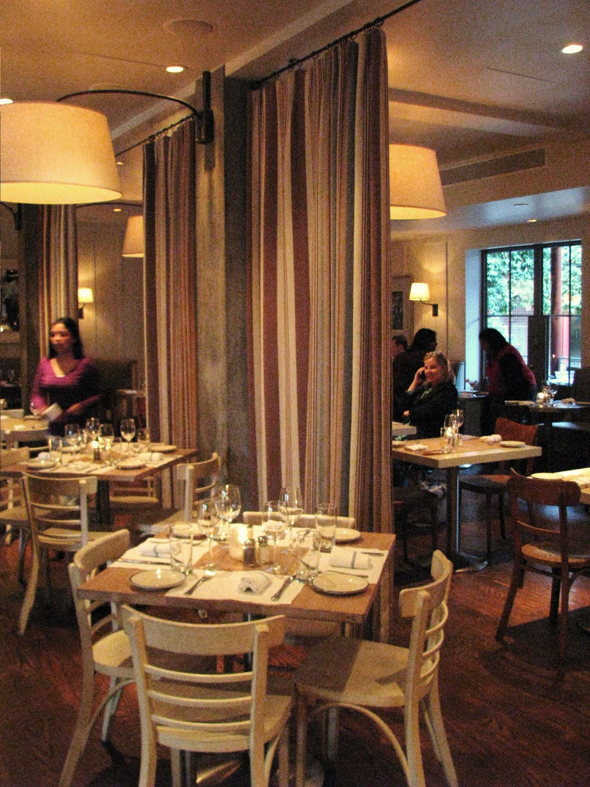 i love the modern farmhouse decor especially the brown ticking stripe curtains that divide the restaurant
