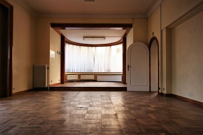 vue de la pièce principale couverte de parquet marqué par la poussière, et une énorme baie vitrée cachée par un épais voilage