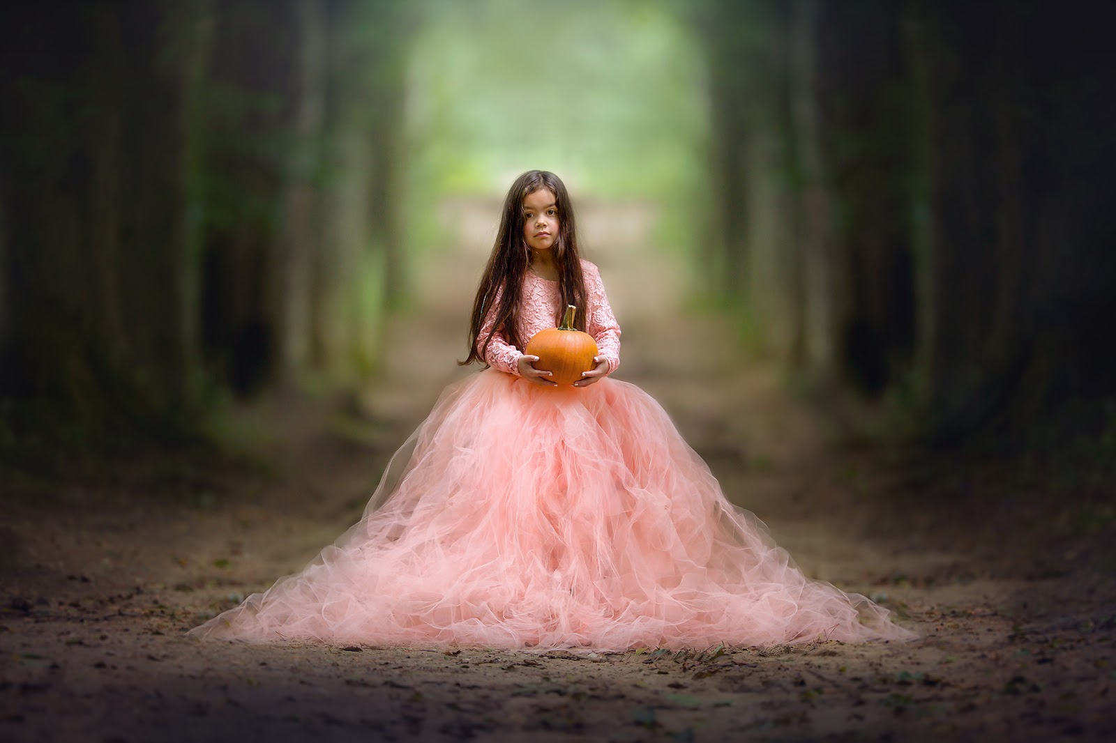 Canon portrait of a young girl in a beautiful red dress standing in an autumn forest with a pumpkin in her hands by Willie Kers