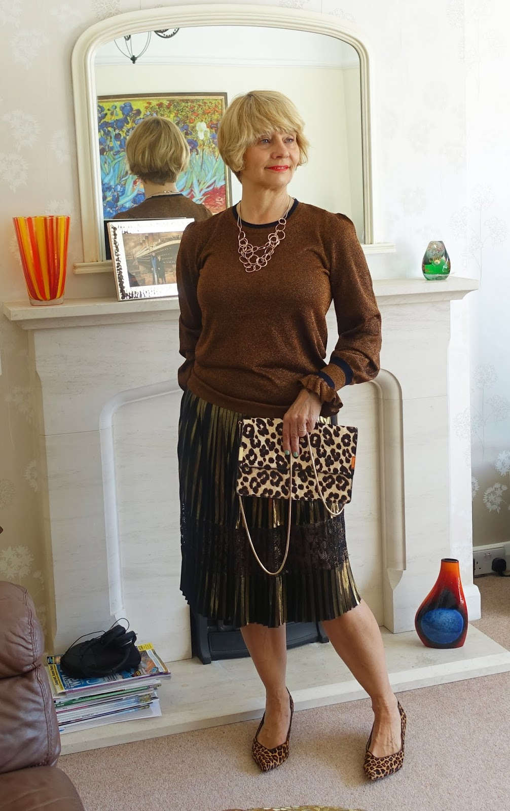 An outfit with transitional qualities for evening stand out, featuring a lurex knitted top with statement sleeves and a gold and black lurex skirt with leopard print accessories.