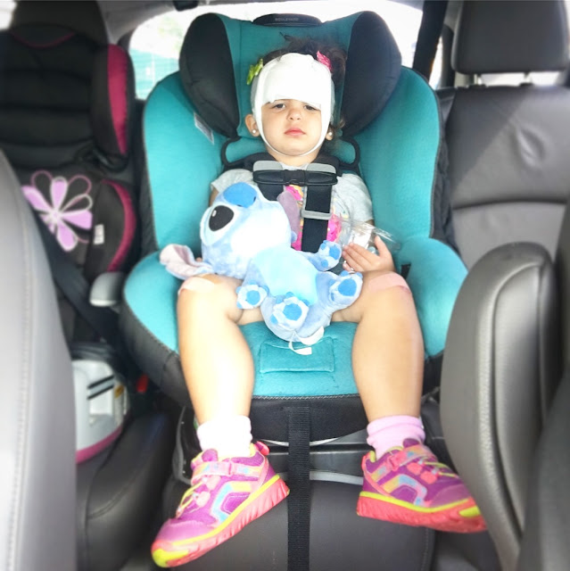 Sad toddler sits in her carseat with stuffed animal in her hand and bandages tied around her head