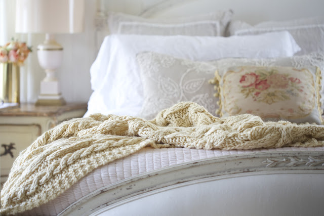 knit blanket with floral pillow on bed