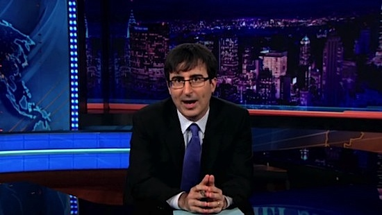 John Oliver, a white man in glasses wearing a dark suit and blue tie with tousled dark hair, on set