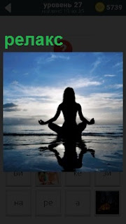 На берегу спокойного моря вечером релакс девушки без одежды в позе для медитации