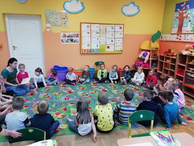 Młodsza i starsza grupa przedszkolna słucha bibliotekarki